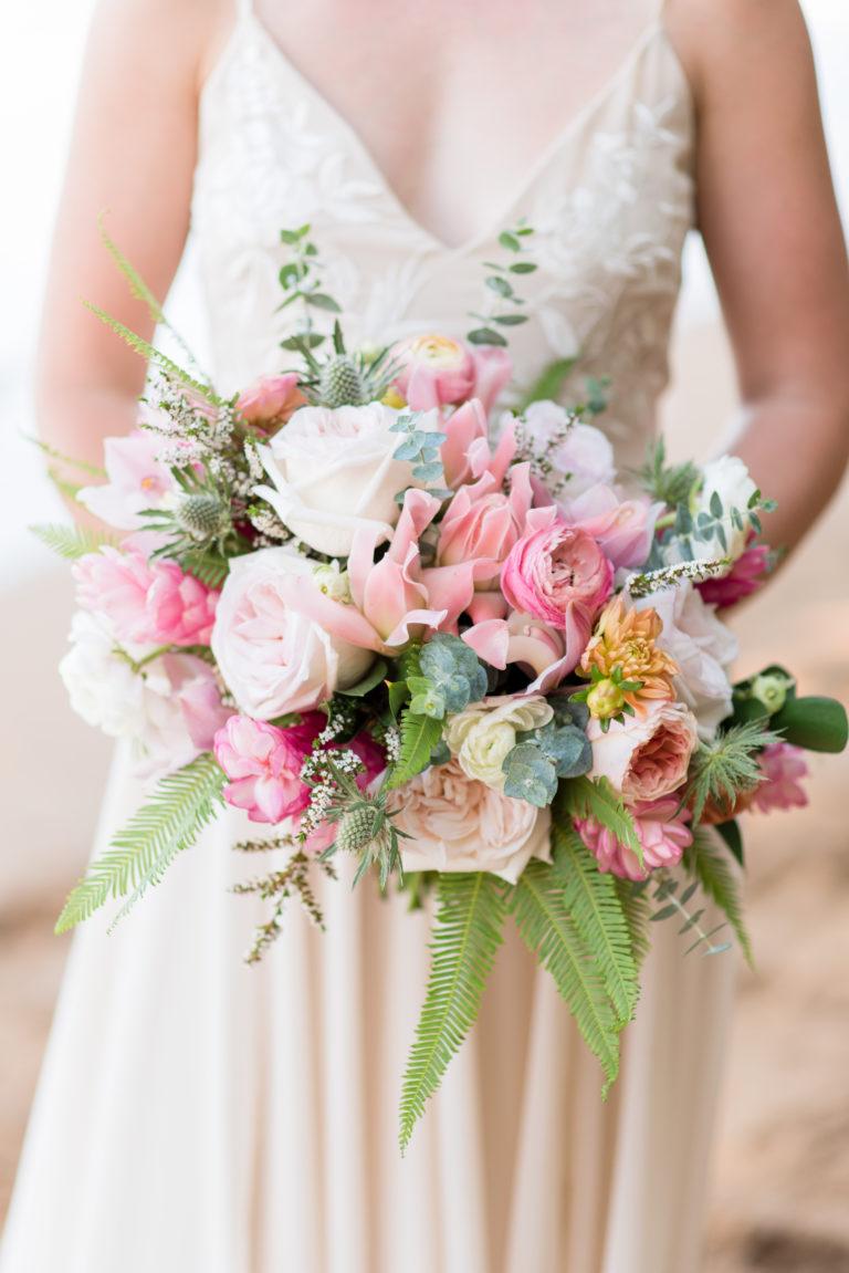 Bride holding Hawaiian flower bouquet.