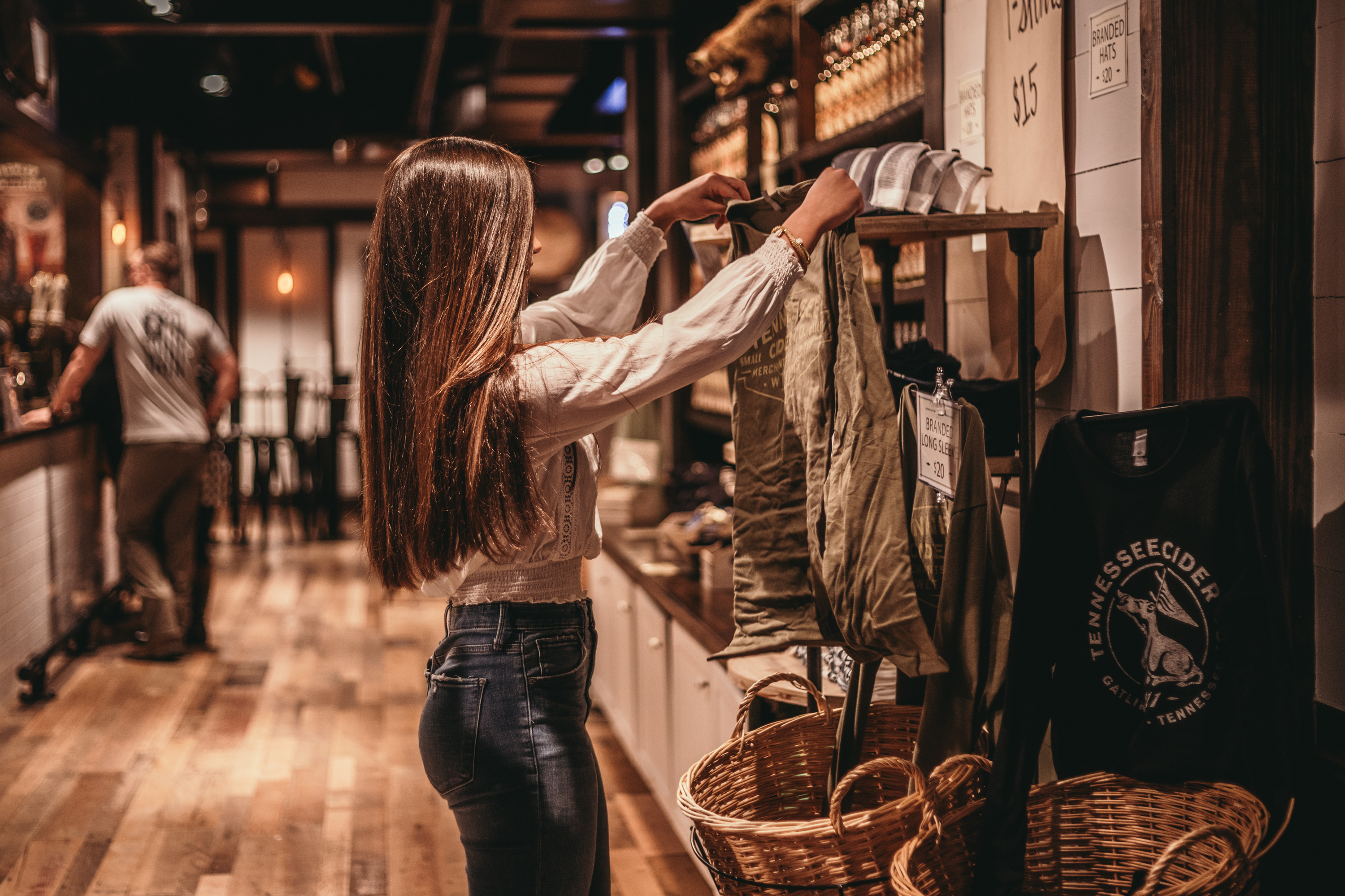 A girl looking at a shirt in Tennessee Cider Company - Tennessee Cider Company offers many products other than cider for your enjoyment in Gatlinburg and Sevierville Tennessee