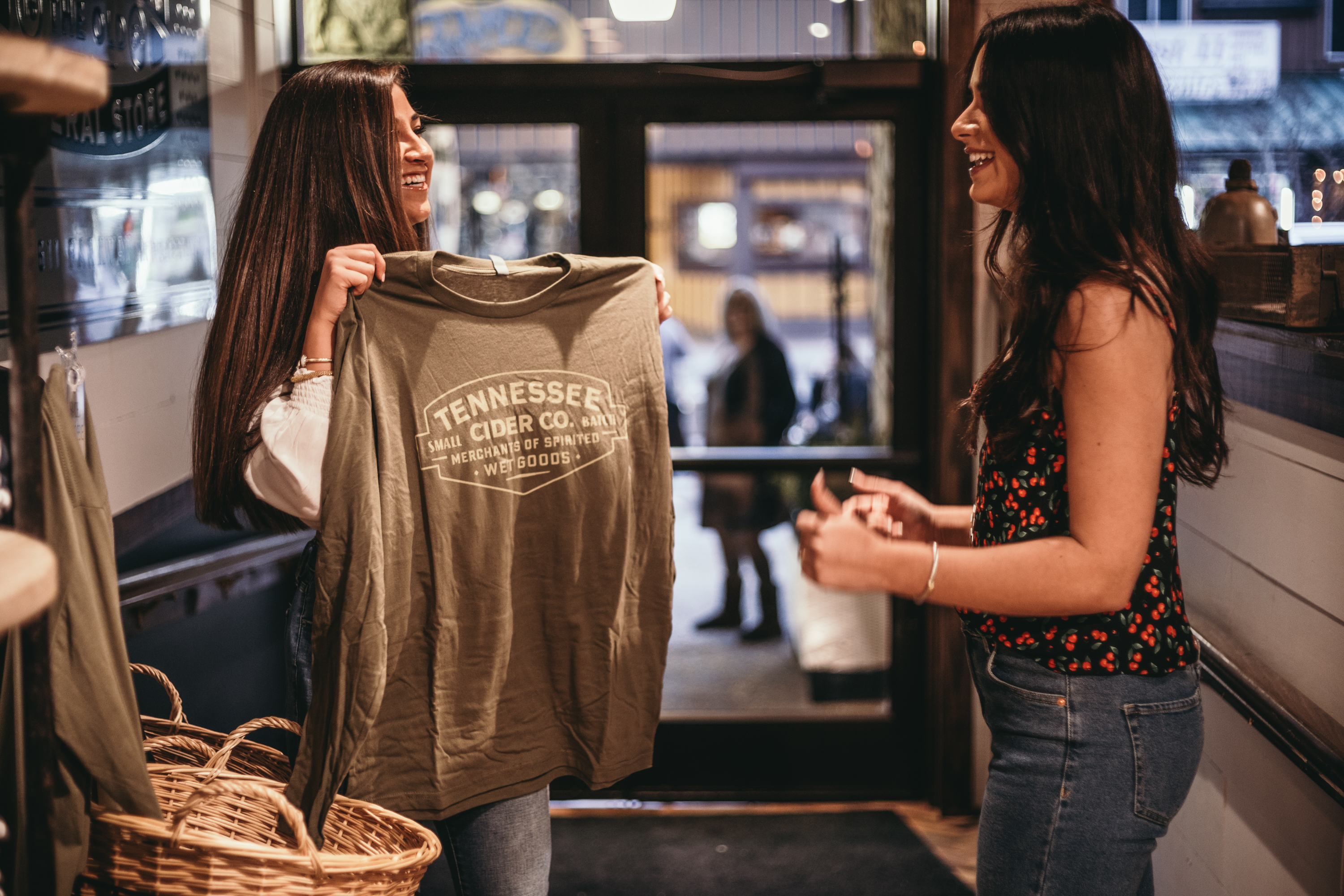 Girls Looking at a shirt in Tennessee Cider Company's retail store -- Tennessee Cider Company offers many products other than cider for your enjoyment in Gatlinburg and Sevierville Tennessee