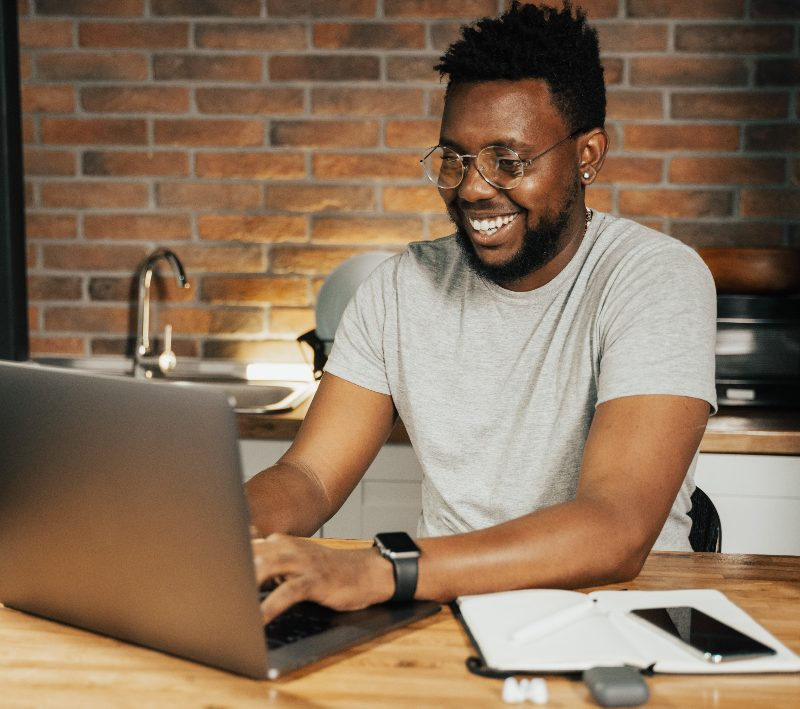 a man working on his computer smiling