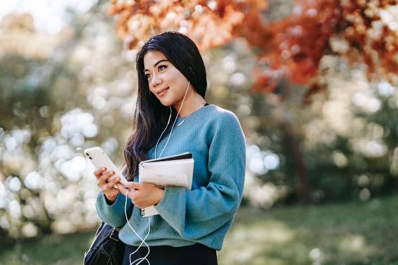 a girl listening to her phone outside