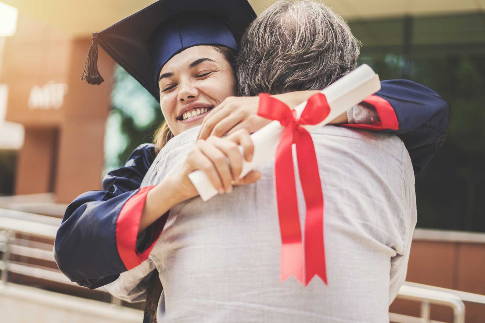 High school graduate hugging parent while holding diploma