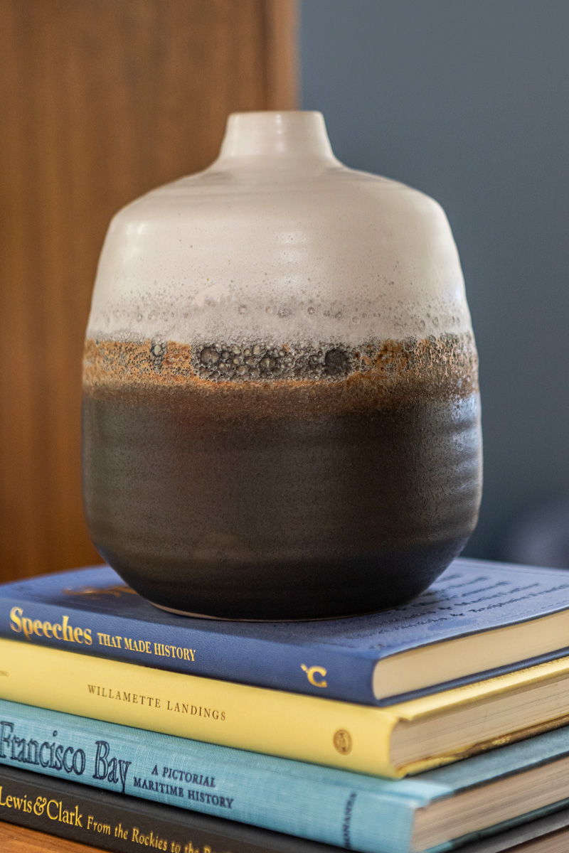 a stoneware vase on a stack of books at the Allium Financial Lake Oswego office.