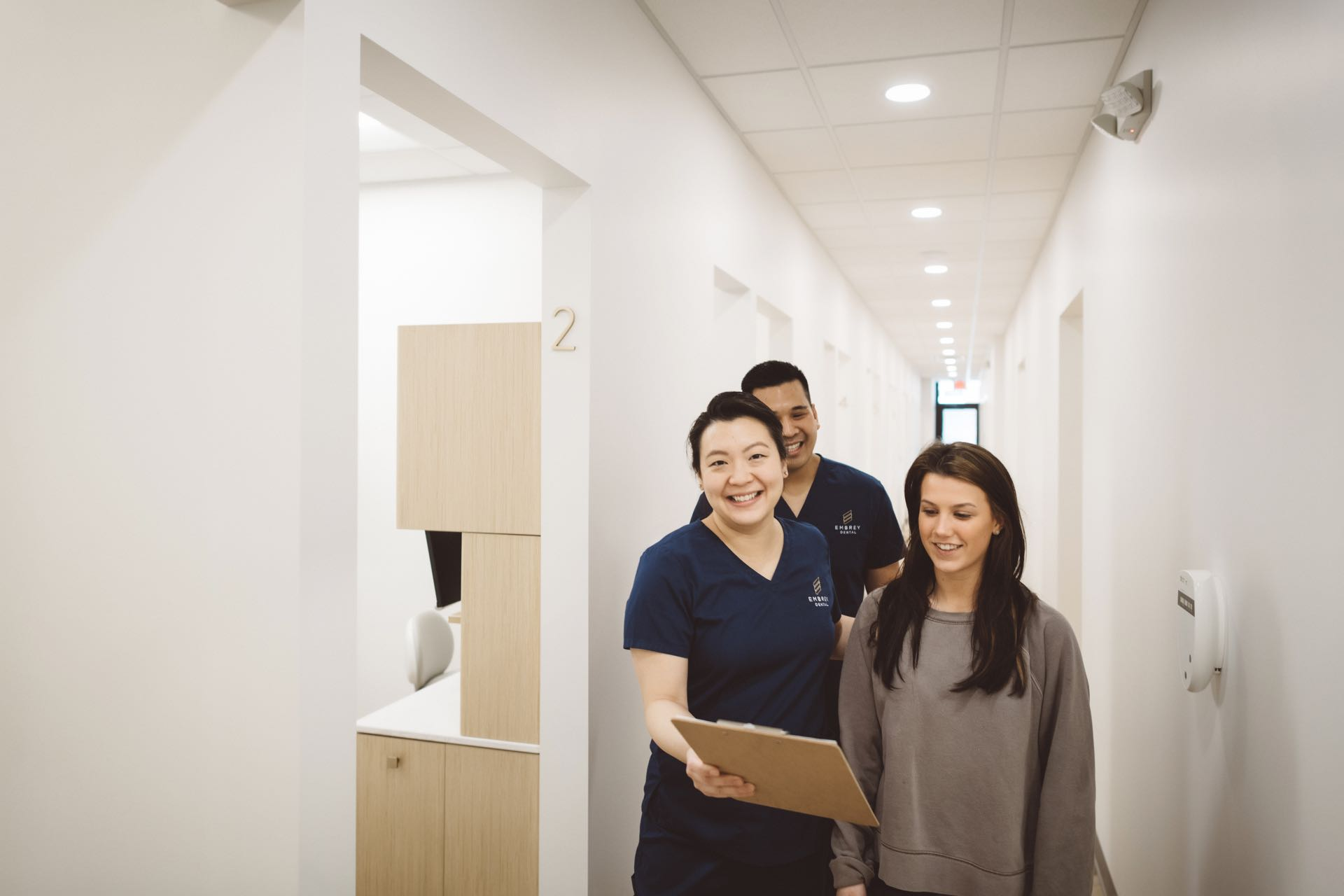 Photo of two Embrey Dental team members and a patient looking at a clipboard