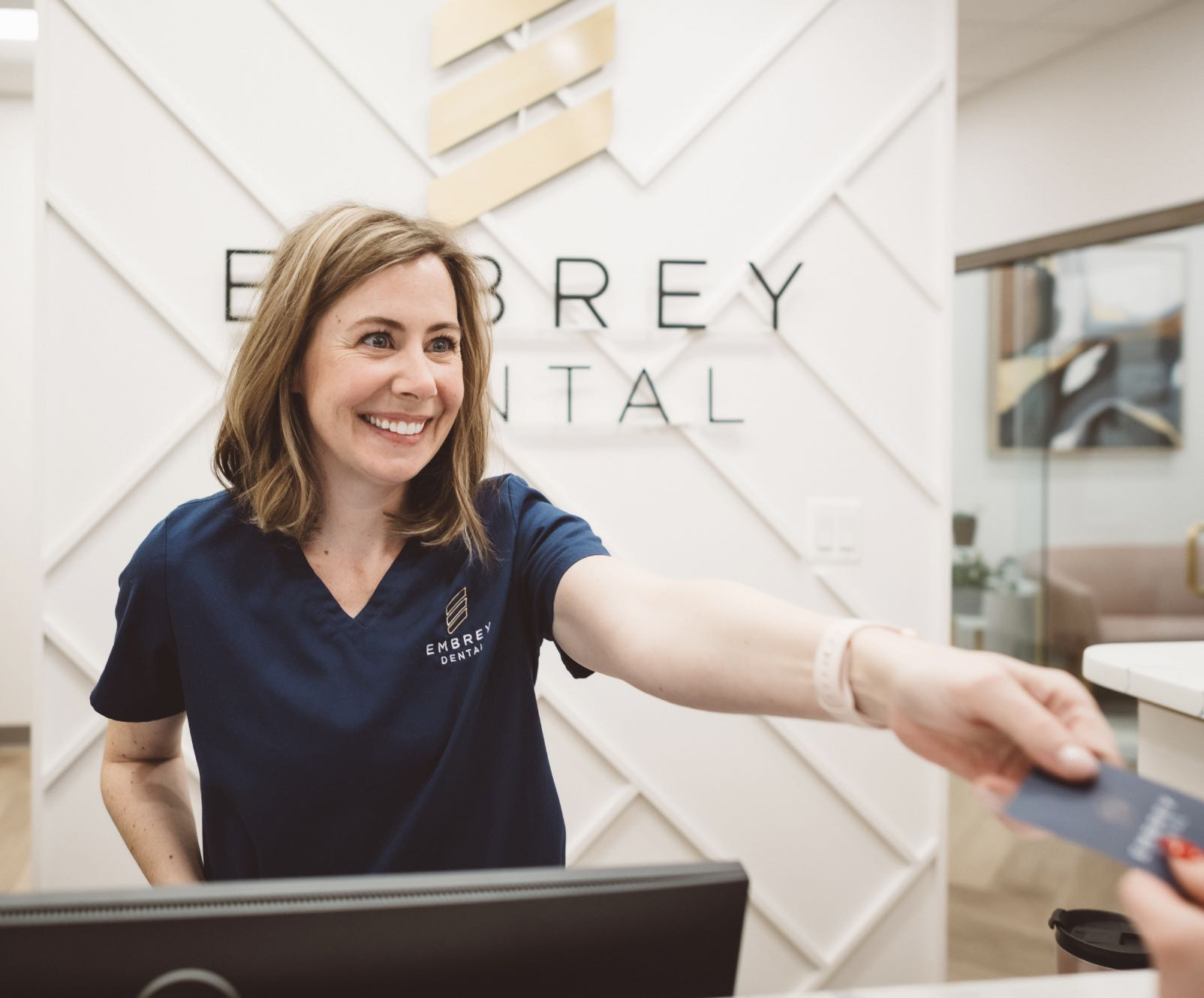 Photo of a smiling Embrey Dental team member reaching out to shake the hand of a patient