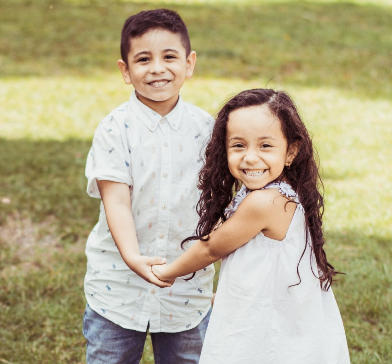 Photo of two smiling children standing outside