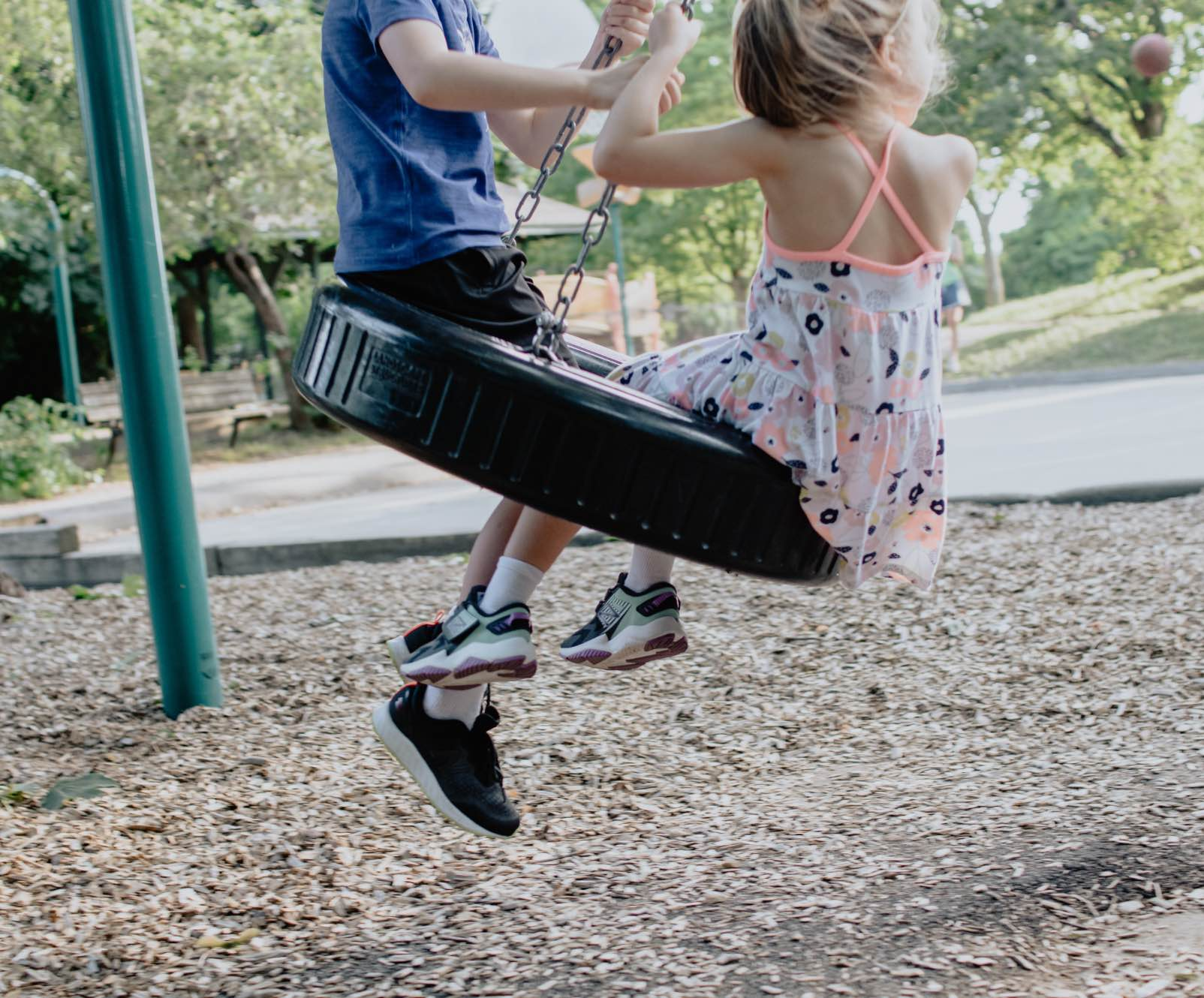 Photo of two children sitting on a tire swing