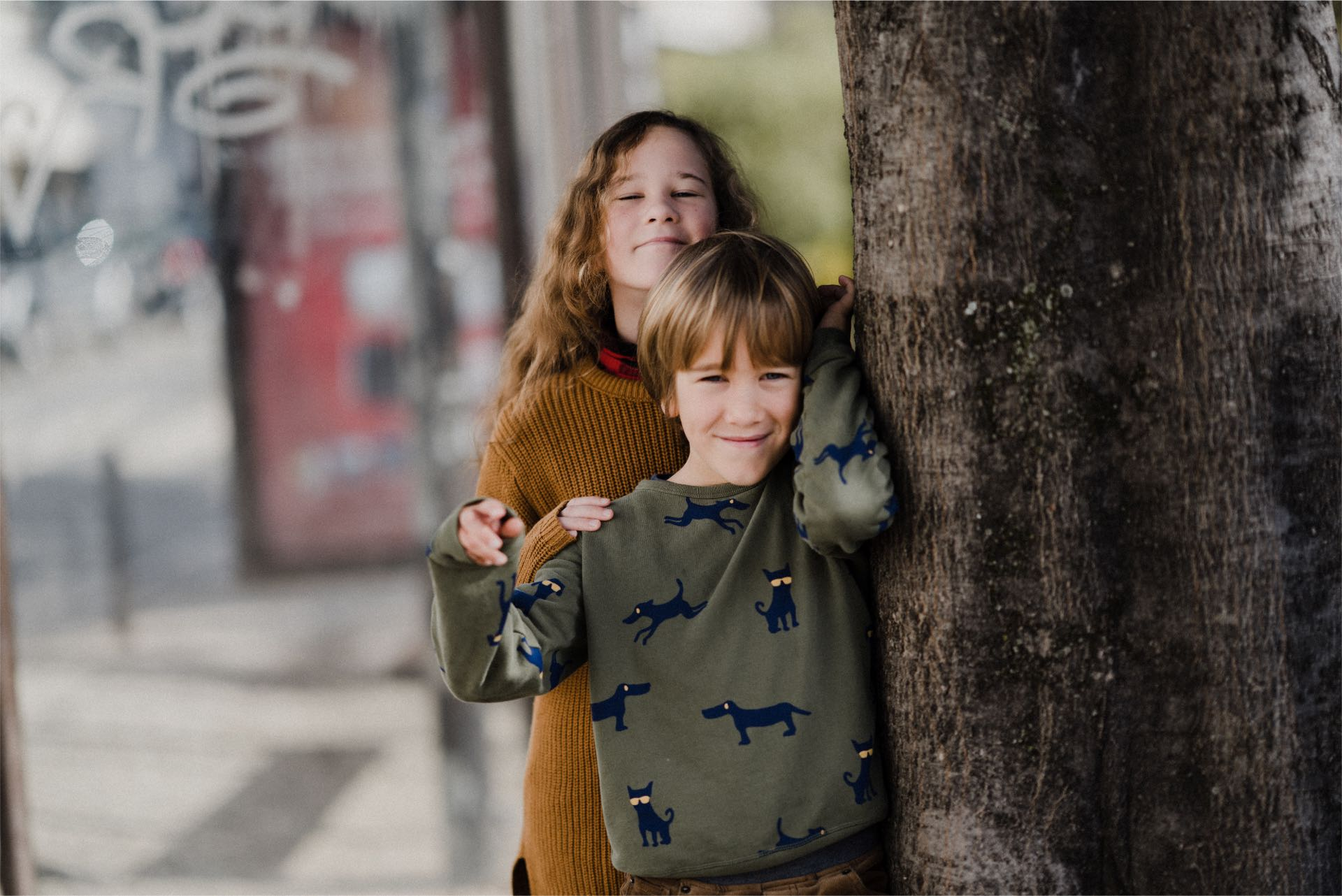 Photo of two children standing beside a tree