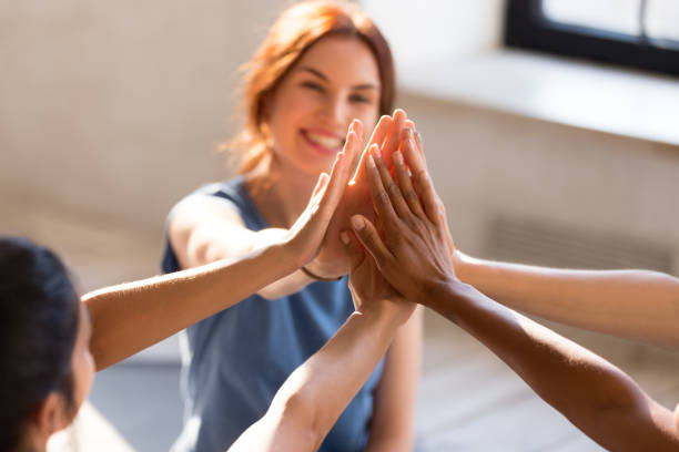Girls giving high five, close up focus on hands Cheerful diverse young girls sitting together in sports studio before starts training giving high five feel happy and healthy, close up focus on hands. Respect and trust, celebration and amity concept female success stock pictures, royalty-free photos & images