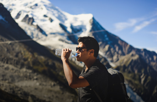 A man drinking clean water while hiking on a mountain