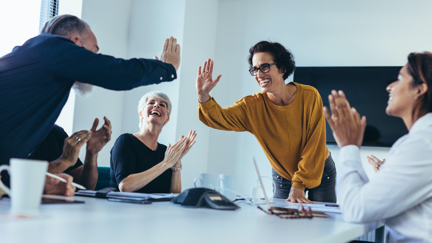 Group of happy laughing people high-fiving in modern office.