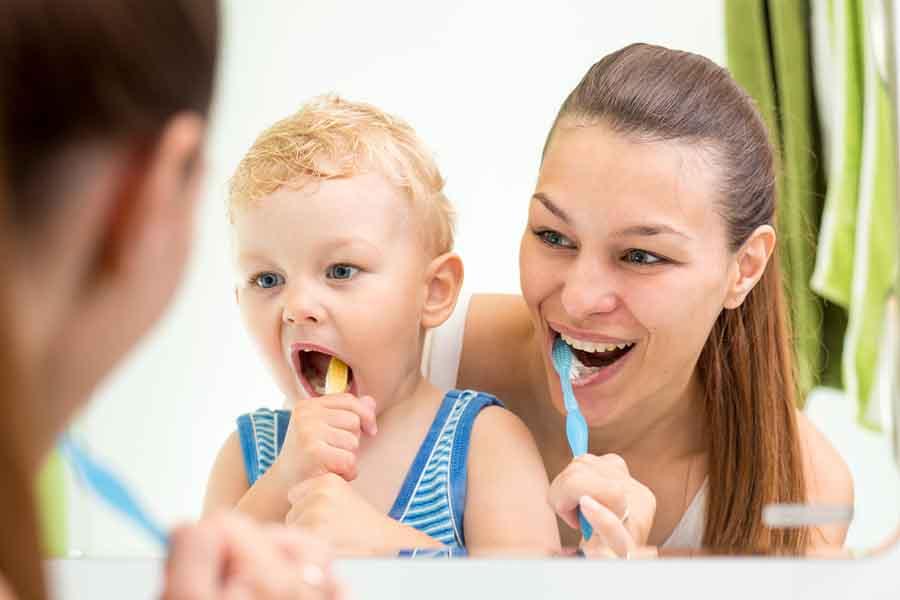 Mother teaching her child proper dental hygiene.
