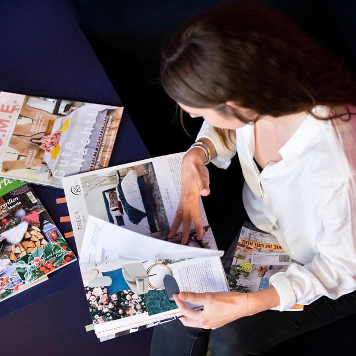 Eine Kollegin von Schröder+Schömbs PR sitzt auf einem Sofa und sucht nach Clippings in Lifestyle-Magazinen.