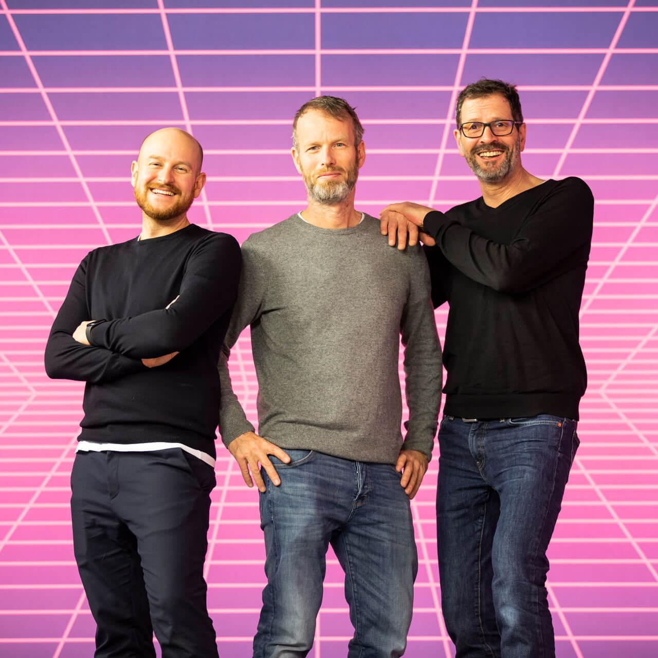 Die Geschäftsführer von Schröder+Schömbs PR, Herbert Schmitz und Michael Hetzinger, posieren vor futurischer Neon-Kulisse mit dem Gründer der Agentur, Gerald Schömbs.