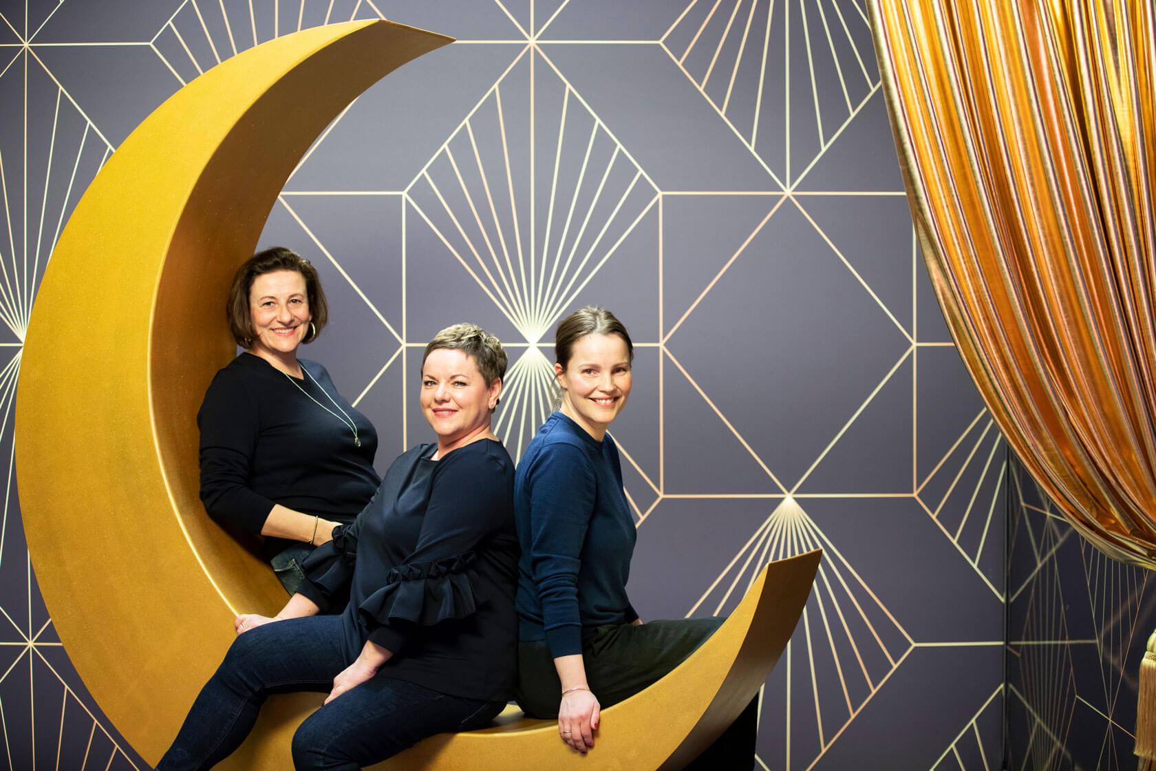 Drei Kolleginnen von Schröder+Schömbs PR posieren für ein Foto in einer Kulisse auf einem gelben Halbmond.