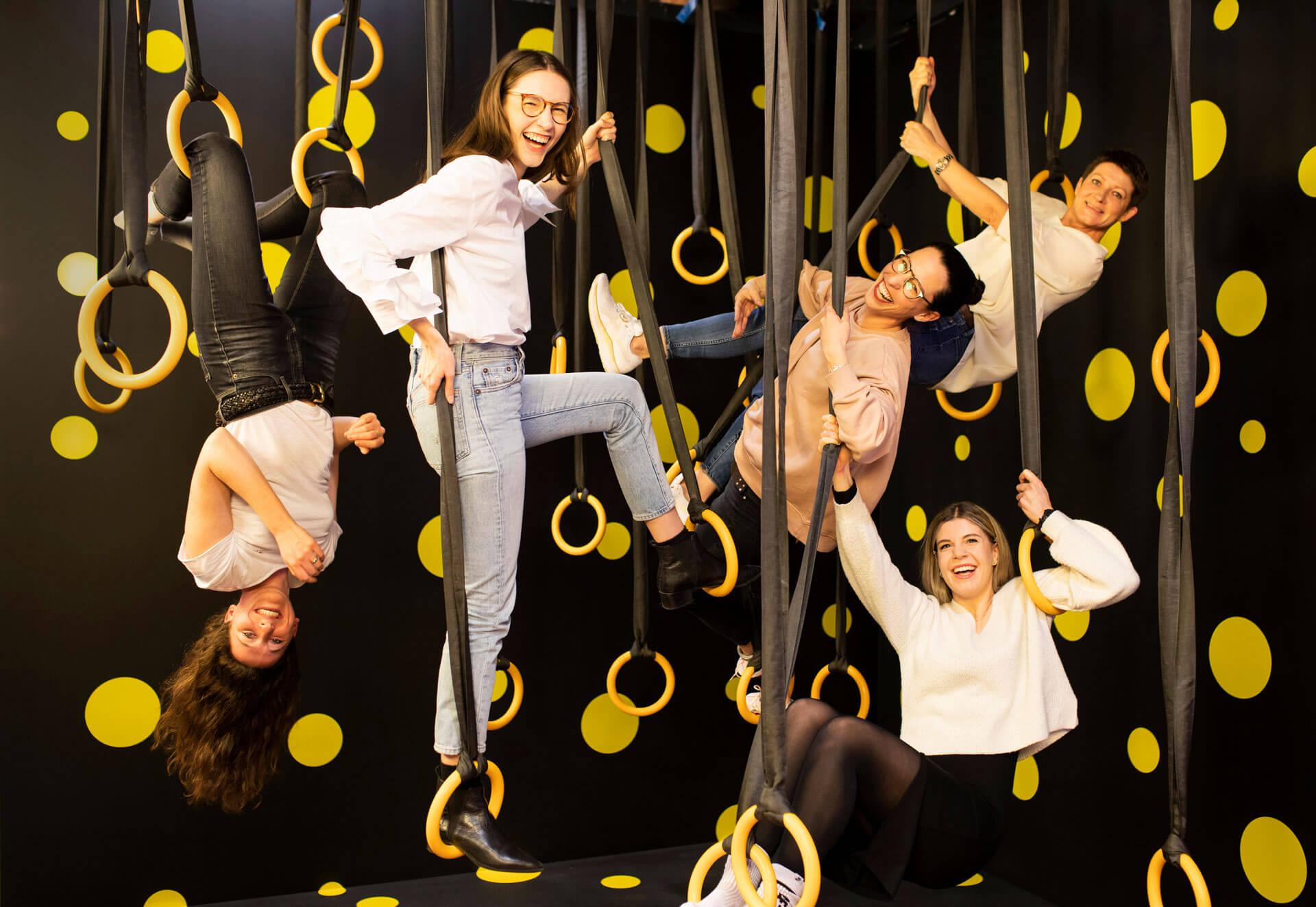 Fünf Kolleginnen von Schröder+Schömbs PR hängen lachend in den Seilen – für ein Fotoshooting.