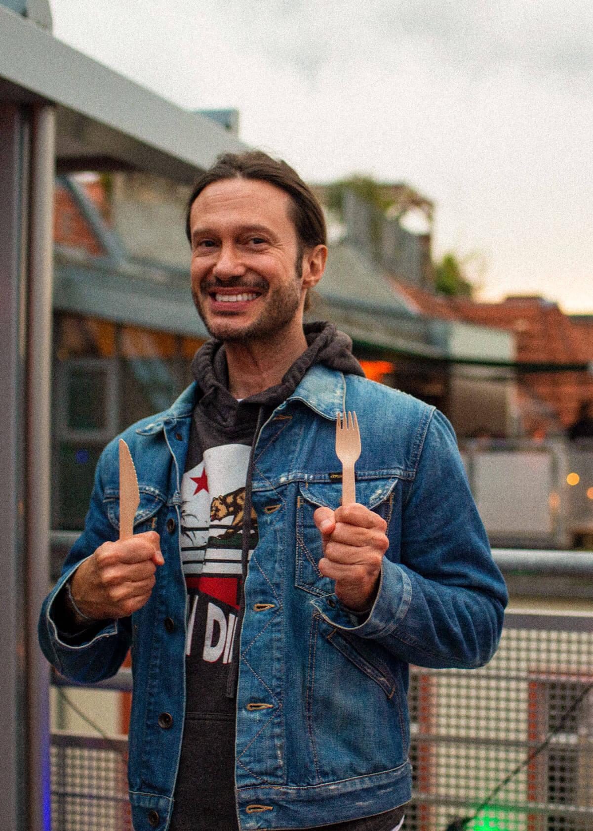 Ein Kollege von Schröder+Schömbs PR freut sich, Holzbesteck in der Hand, auf das Essen bei einer Party.
