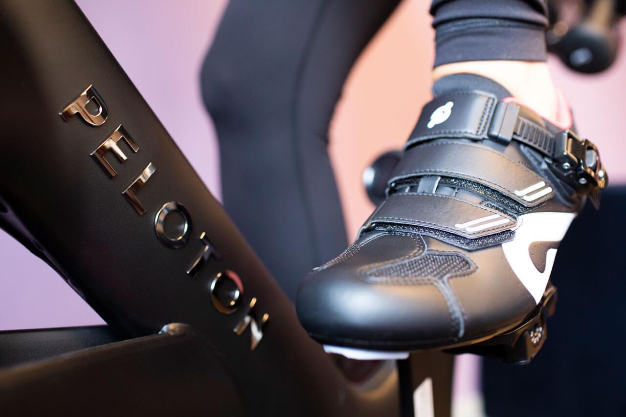 Eine Nahaufname eines Schuhs, der in die Pedale eines Peloton Bikes tritt.
