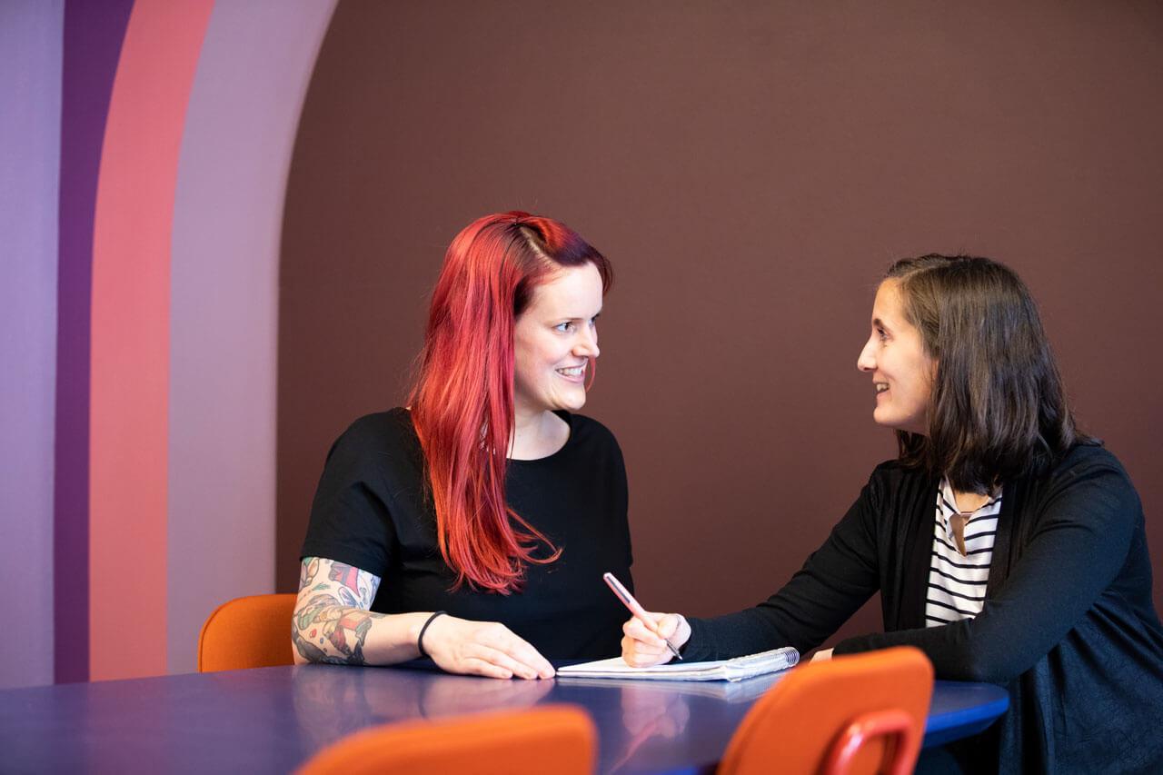 Zwei Kolleginnen von Schröder+Schömbs PR sprechen miteinander in einem Meeting.