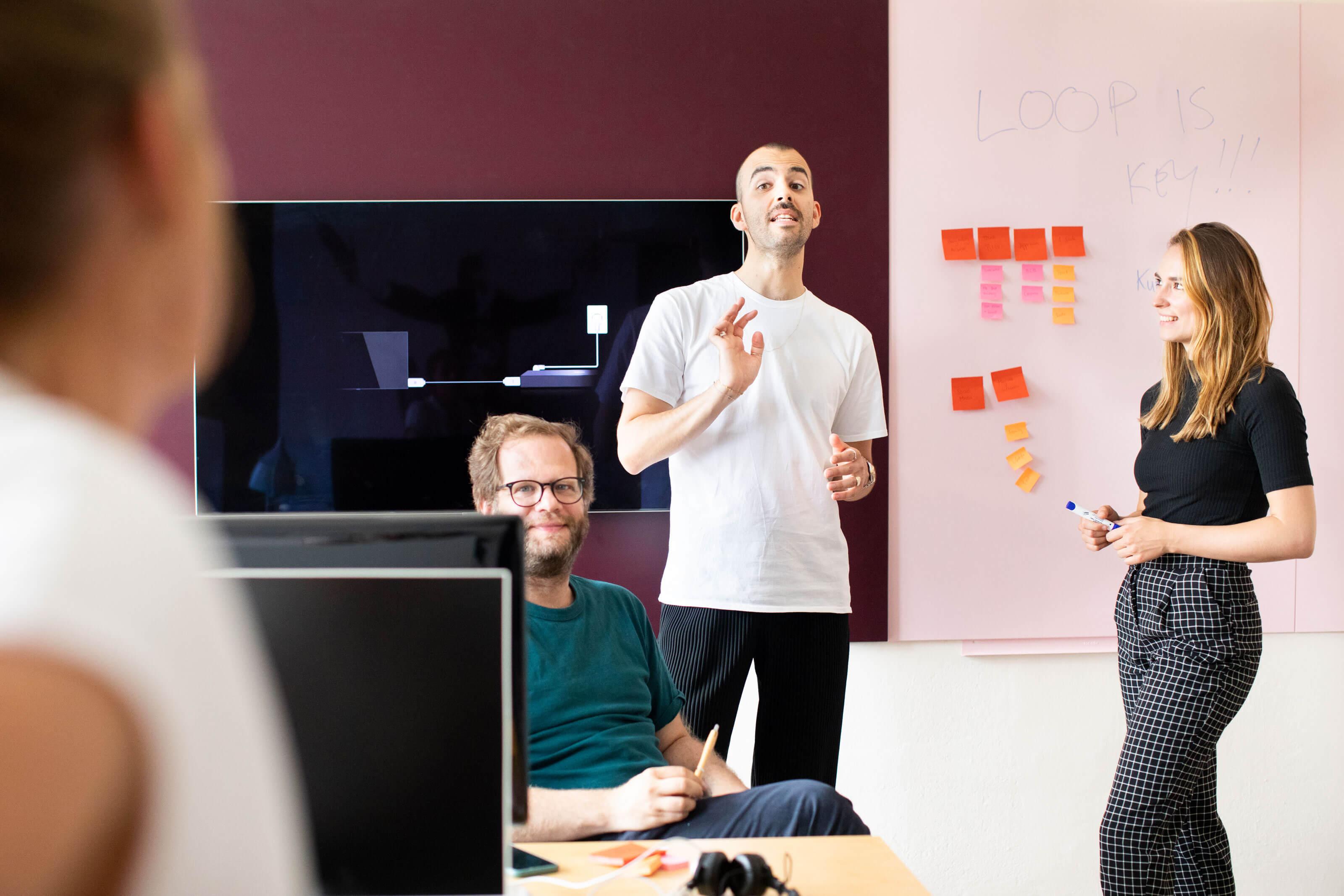 Das Team Strategie und Konzeption bei Schröder+Schömbs PR diskutiert angeregt in einer Besprechung.