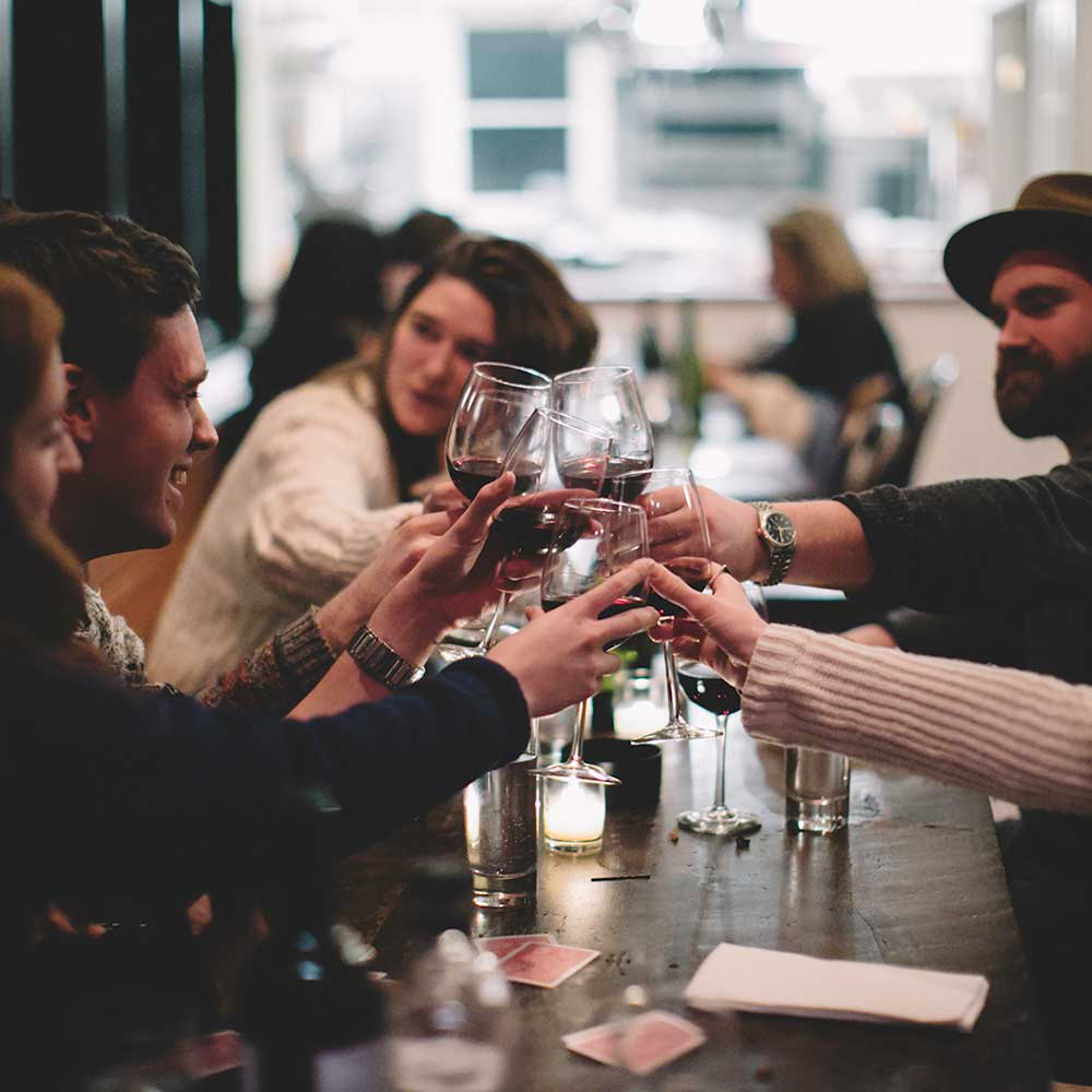 group of friends drinking wine and cheersing