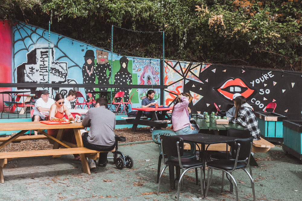 Sisters & Brothers outdoor eating space with a mural
