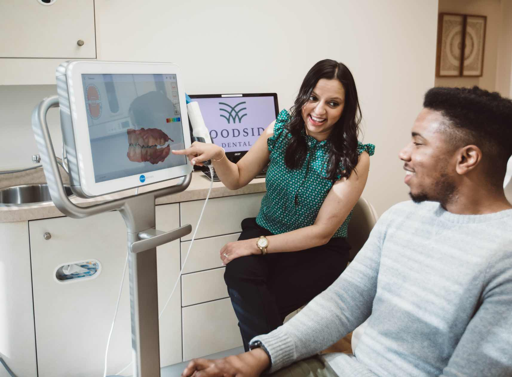 Photo of Columbia Maryland dentist Dr. Shah showing a 3-D dental scan to a patient