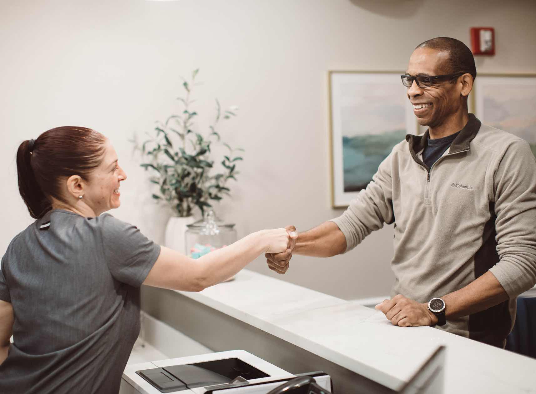 Photo of a Woodside team member shaking hands at the front desk with a patient