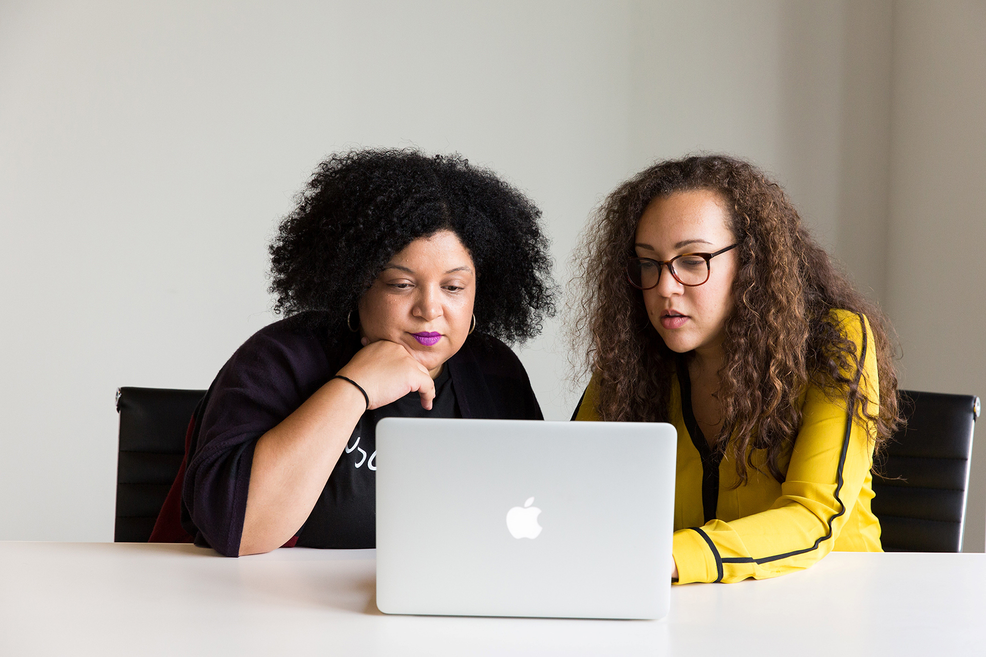 Two women working on a laptop at a table