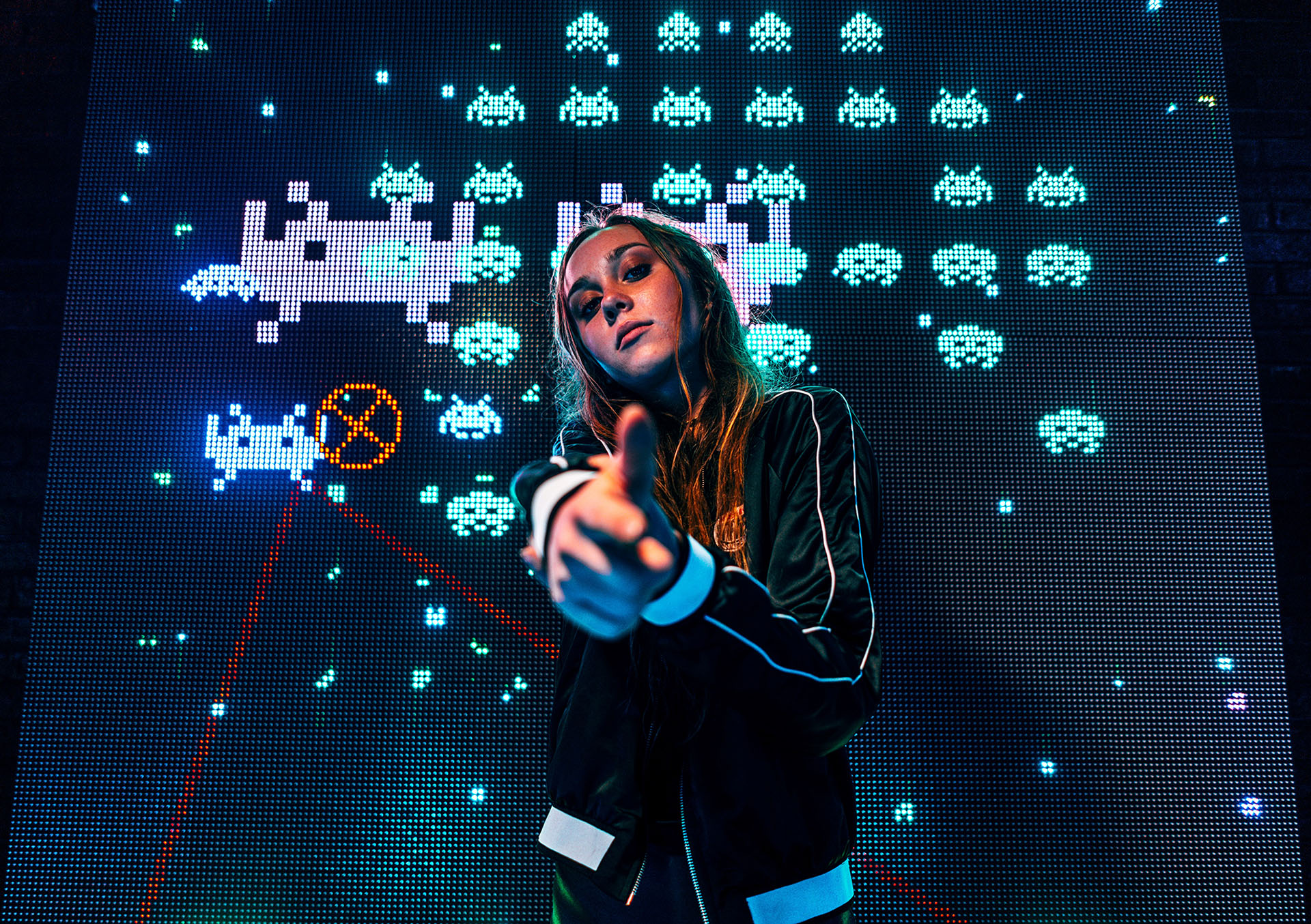 Young woman pointing at the camera in front of a gaming screen