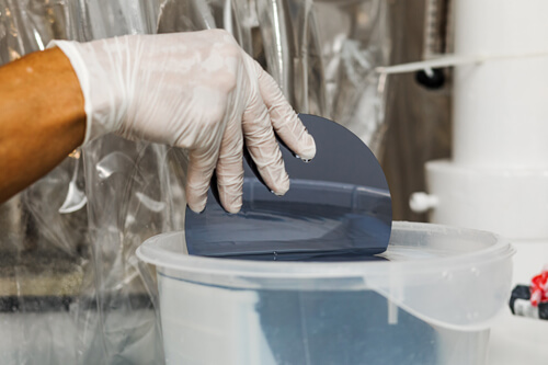 Gloved hand placing a silicon wafer into a storage device.