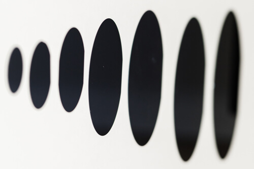 Row of germanium wafers on a blank backdrop.