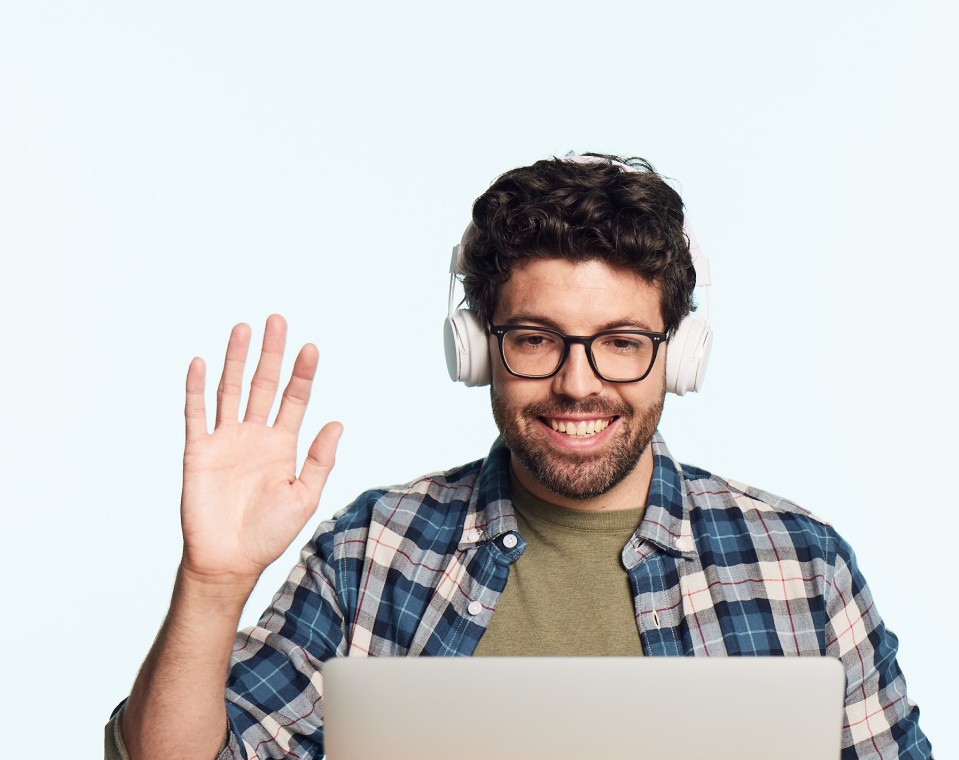 Photo of a friendly male Juni instructor waving at the computer screen during a Juni course