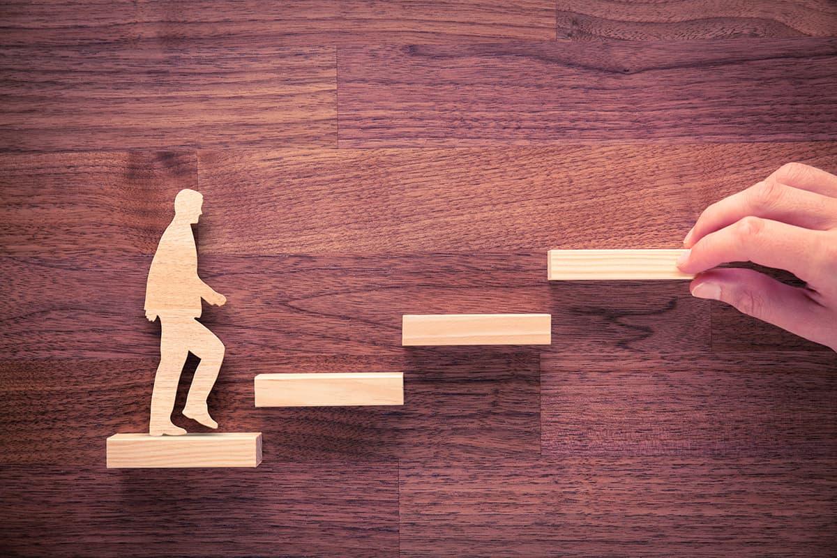 Wooden man walking up wooden steps.