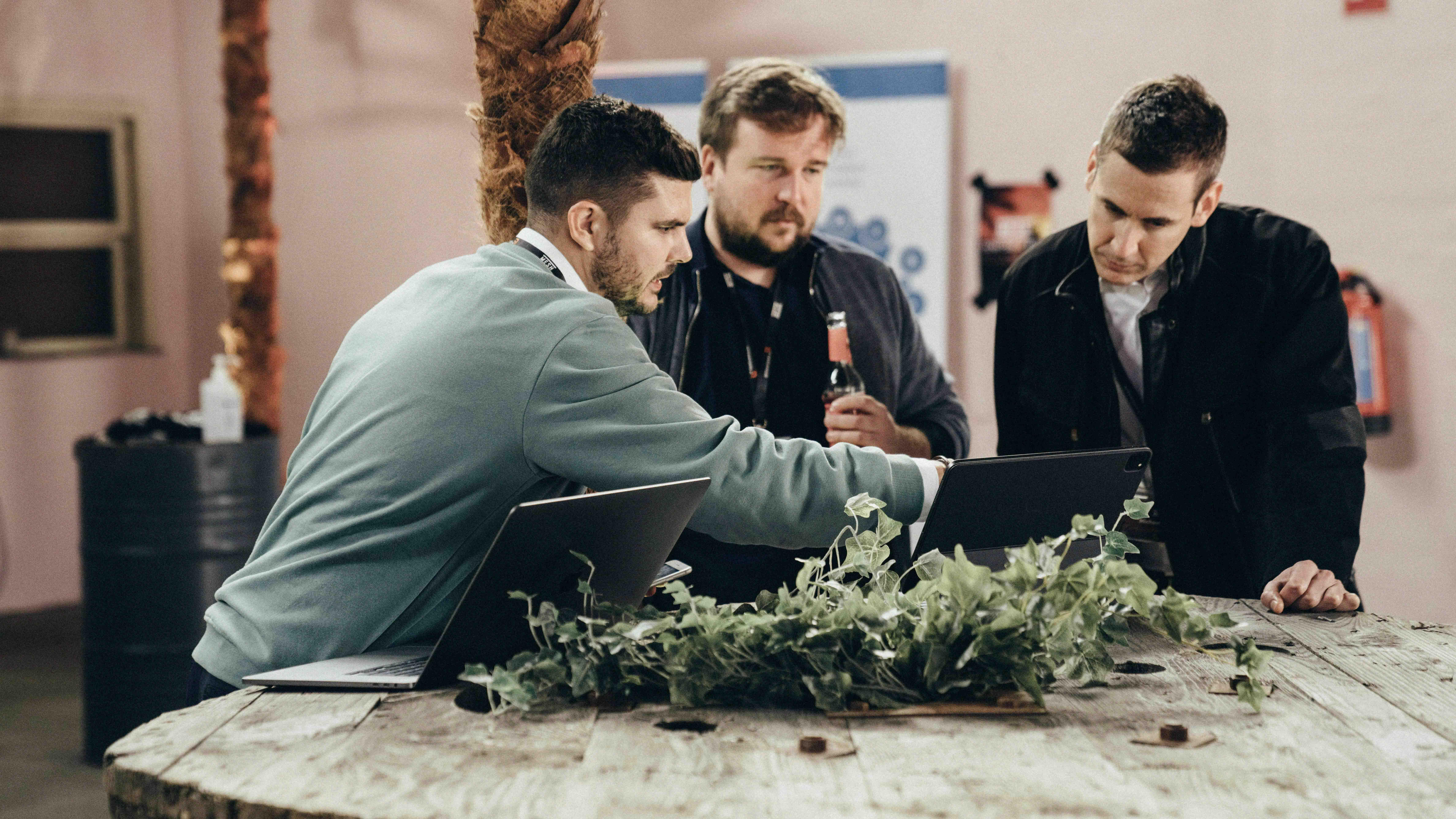 Männer unterhalten sich vor Laptops.