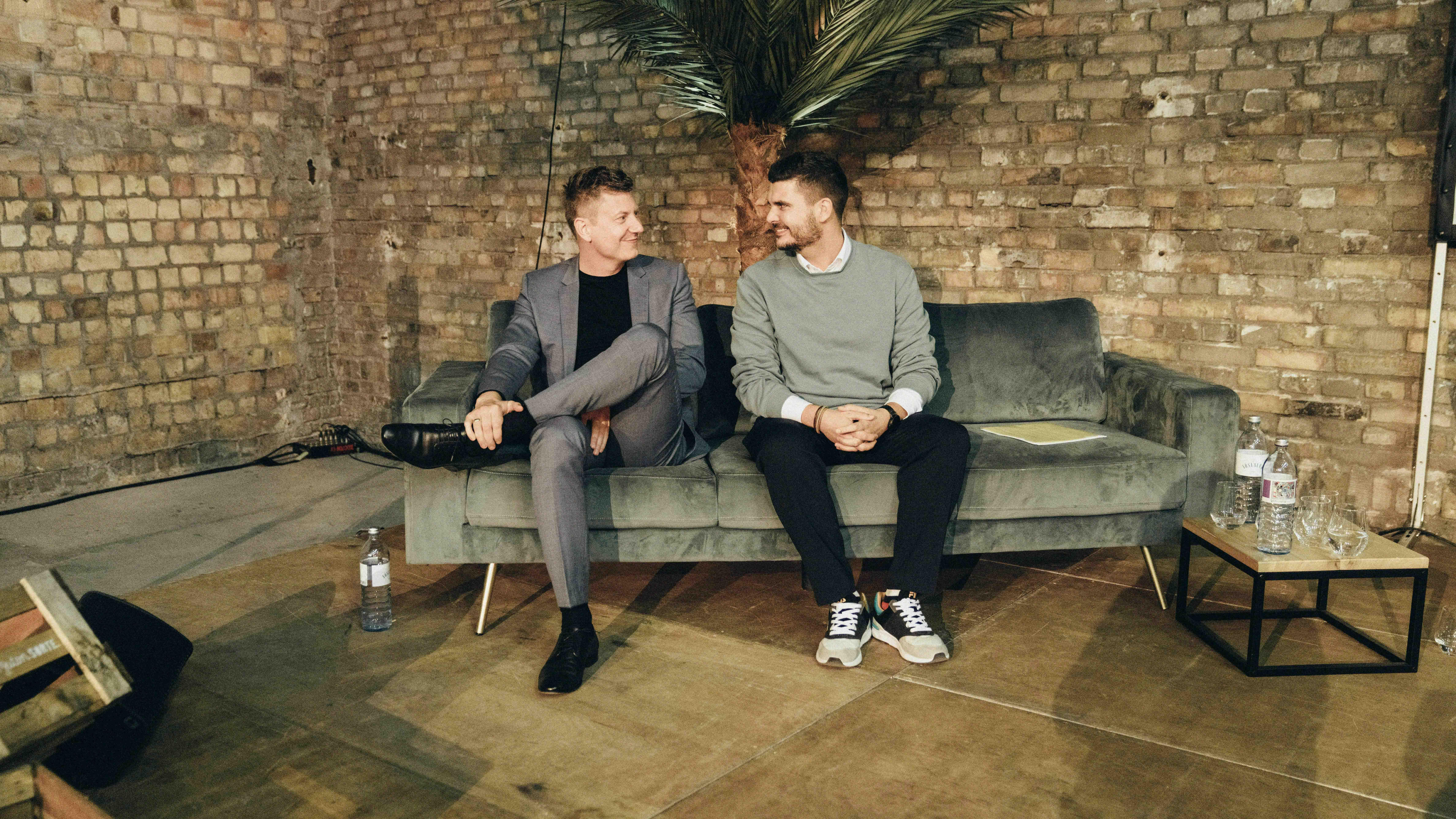 Nils Fortmann und Matthias Stubbe sitzen auf einer Couch.