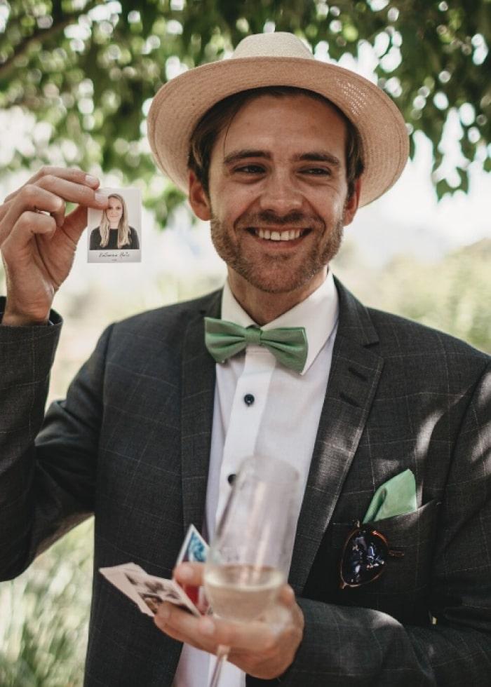 Hochzeitsgast hält lachend seinen Sticker in die Kamera
