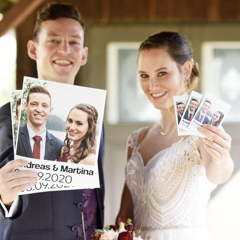 Brautpaar hält lachend Stickerpacks und Alben in die Kamera