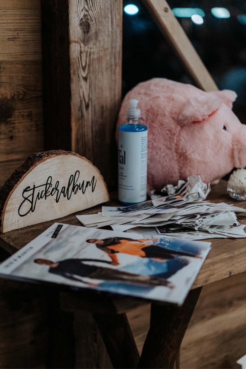 Stickeralbum und Stickerpakete auf einer Hochzeit, im Hintergrund Desinfektionsmittel
