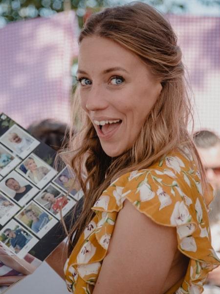 Hochzeitsgast Ricarda lachend mit einem Stickeralbum in der Hand
