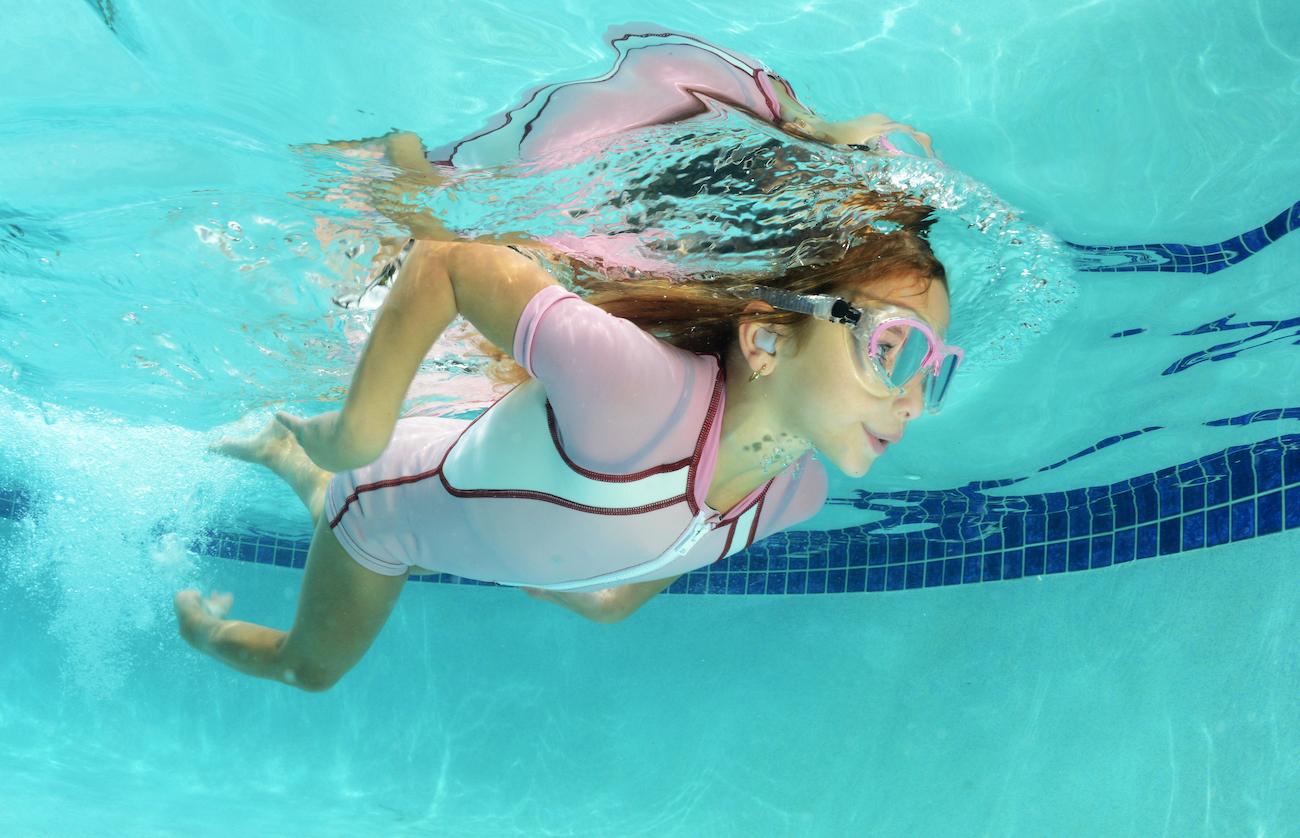 girl swimming wearing swim plugs