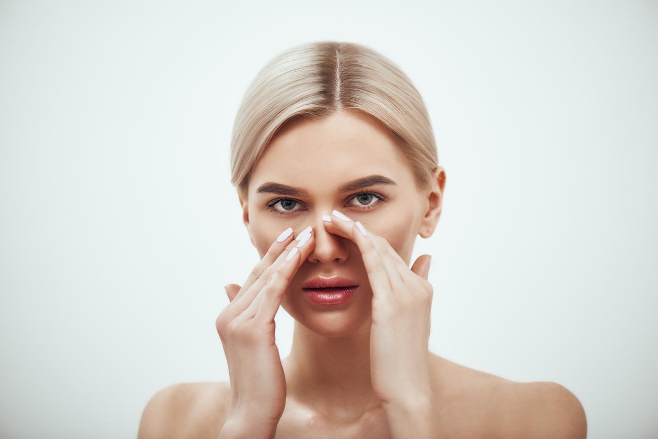 blonde woman touching nose