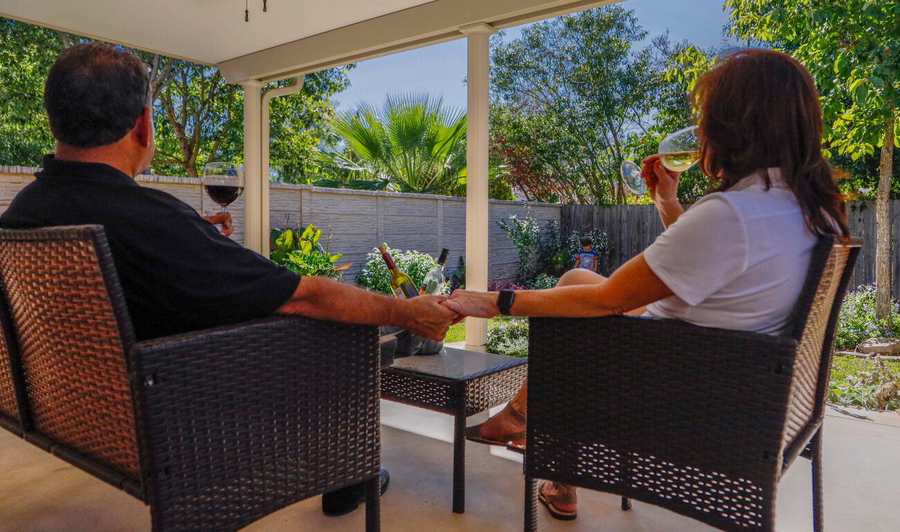 A couple sitting under their patio cover holding hands while sipping glasses of wine.
