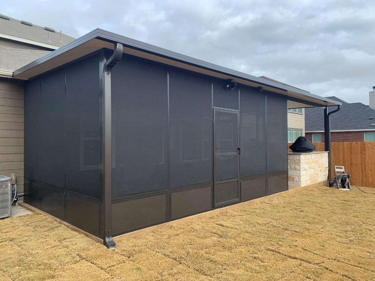 A patio enclosure with screens and a flush screen door leading into the enclosure.