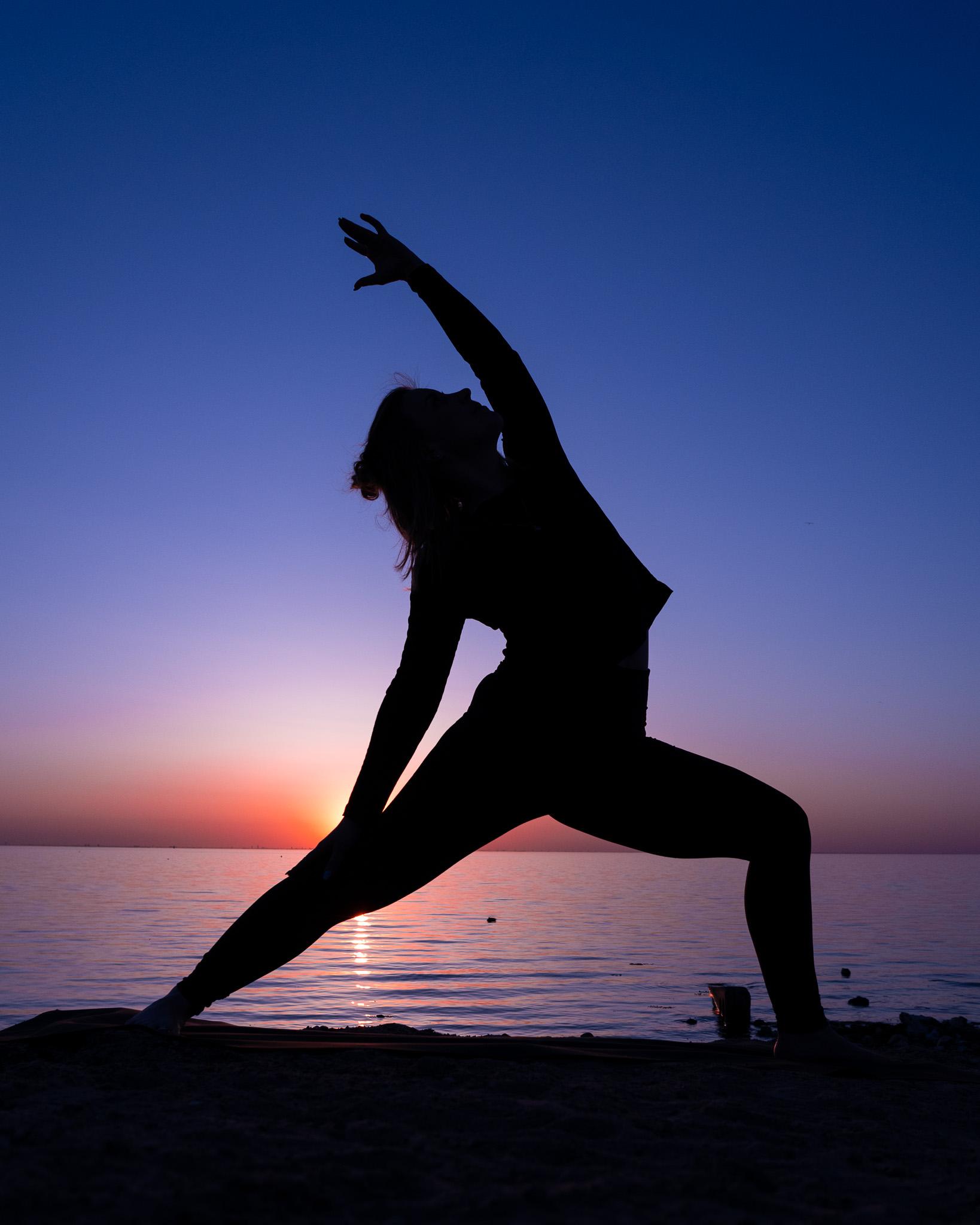 Girl doing yoga in sunset sunrise