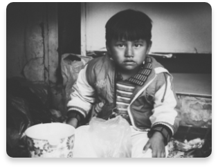 Black and white photo of a sad child in poor living conditions.