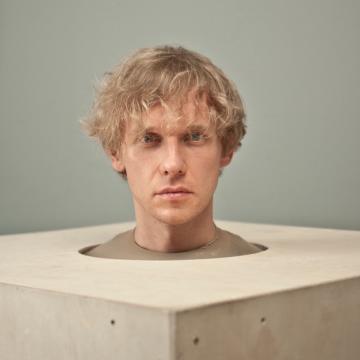Фото-портрет кудрявого светловолосого мужчины, голова которого торчит из круглого отверстия в деревянном кубе.