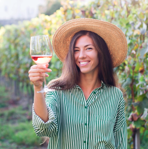 Woman in vineyard holding a glass of wine
