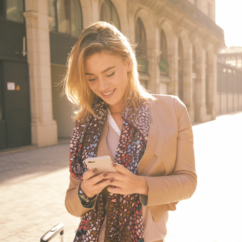 Woman smiling whilst looking at her mobile phone