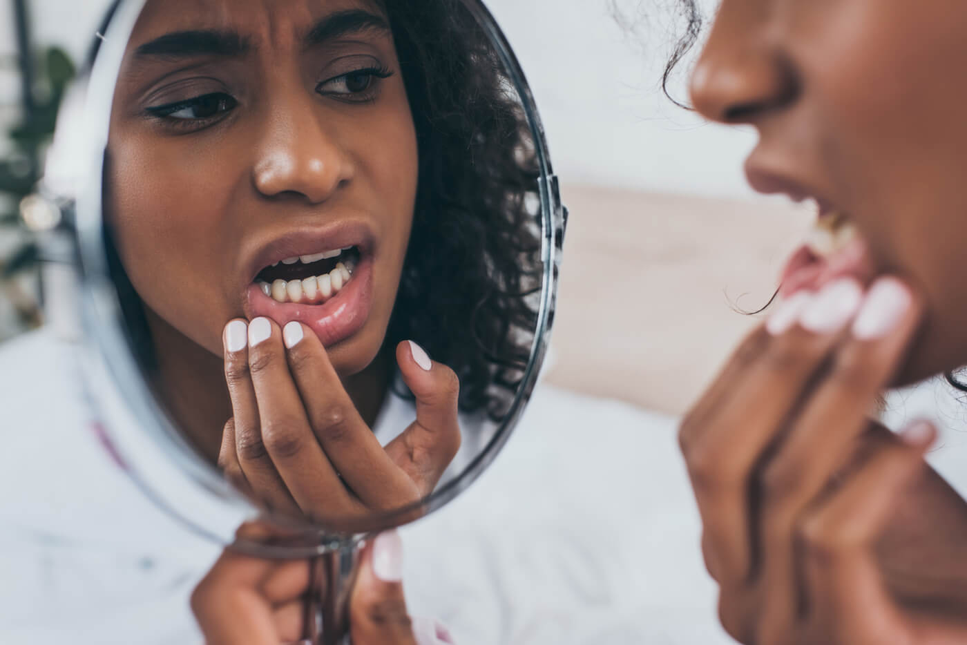 Woman with tooth pain looking in mirror